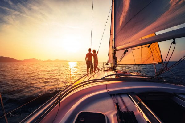 couple looking out at sunset across the ocean on a yacht
