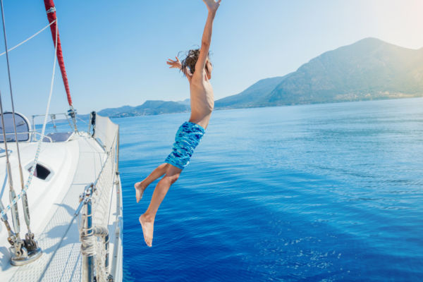 Boy jump in sea of sailing yacht on summer cruise. Travel adventure, yachting with child on family vacation